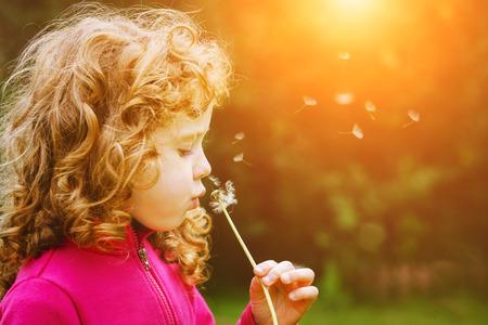 Foto de Girl blowing dandelion in the rays of the sun. Toning for instagram filter. - Imagen libre de derechos