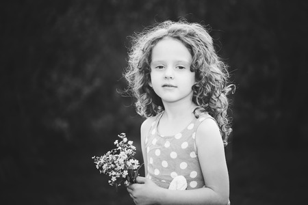 Photo for Beautiful little girl with a flower in her hand. Black and white photo. - Royalty Free Image