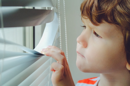 Photo for Little child looking out the window through the blinds.        - Royalty Free Image