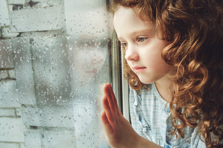 Photo pour Sad child looking out the window. Toning photo. - image libre de droit