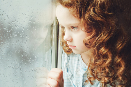 Foto de Sad child looking out the window. Toning photo. - Imagen libre de derechos