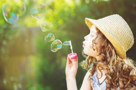 Photo pour Cute girl blowing soap bubbles in a heart shape. Happy childhood concept.  - image libre de droit