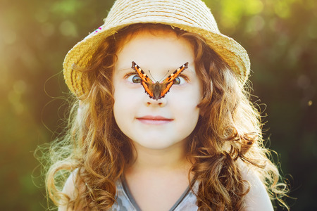 Photo pour Surprised girl with a butterfly on her nose, focus on a girl\'s face. - image libre de droit