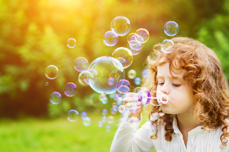 Photo pour A little girl blowing soap bubbles in summer park. Background toninf for instagram filter. - image libre de droit