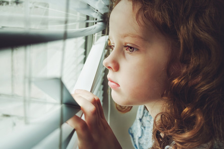 Photo for Sad little girl looking out the window through the blinds. Background toning to instagram filter. - Royalty Free Image