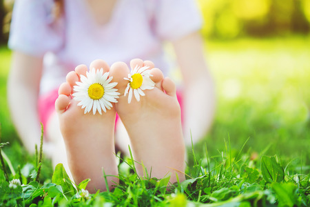Foto de Child feet with daisy flower on green grass in a summer park. - Imagen libre de derechos