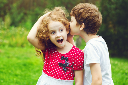 Photo for Little boy and girl whispers. - Royalty Free Image