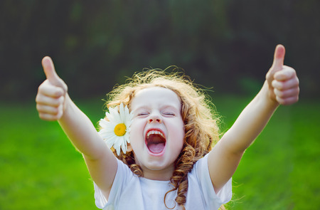 Foto per Laughing girl with daisy in her hairs, showing thumbs up. - Immagine Royalty Free
