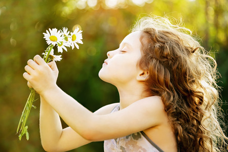 Photo pour Girl smelling a bouquet of daisies, photo in the profile. Healthy breathing. Instagram toning, sunset light. - image libre de droit