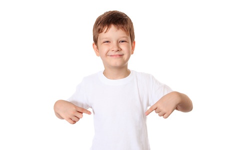 Photo pour Happy little boy pointing his fingers on a blank t-shirt, a place for your advertising. - image libre de droit