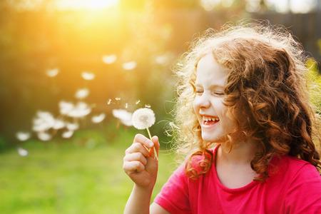 Foto de Little curly girl blowing dandelion in sunset light. Instagram filter. Healthcare, medical concept. - Imagen libre de derechos