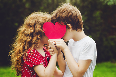 Photo pour Cute children holding red heart shape in summer park. Valentines day background. - image libre de droit