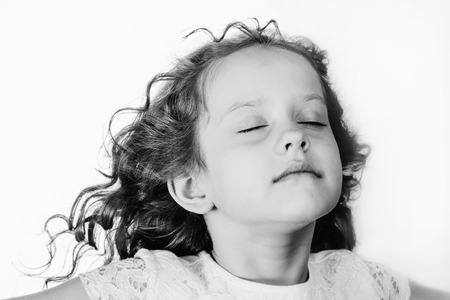 Foto de Little girl closed her eyes and breathes the fresh air. Black and white portrait. - Imagen libre de derechos