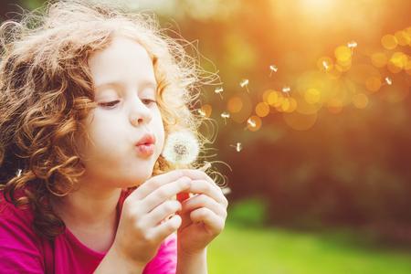 Foto de Little curly girl blowing dandelion. - Imagen libre de derechos