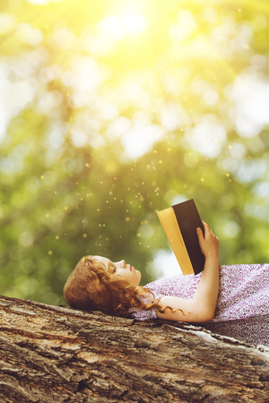 Photo pour Serious little girl reading the Bible or a book on a big tree in the rays of sunset. - image libre de droit