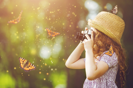 Foto de Little girl in straw hat, rustic style dress, photographing butterfly with retro photo camera in fairytale forest. - Imagen libre de derechos