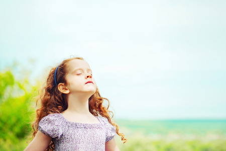 Photo for Little girl closed her eyes and breathing with fresh blowing air. Health and medical concept. - Royalty Free Image