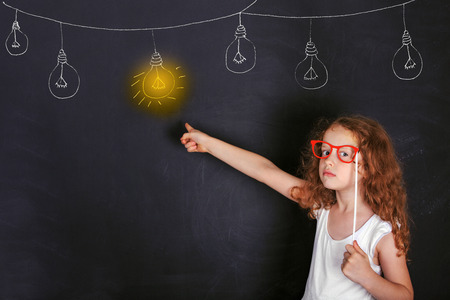 Photo pour Smart child with red glasses points a finger at lighted lamp. Education and Leadership concept. - image libre de droit