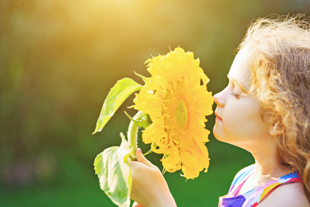 Foto de Joyful child smell sunflower enjoying nature in summer sunny day. Healthcare, freedom and happy childhood concept. - Imagen libre de derechos