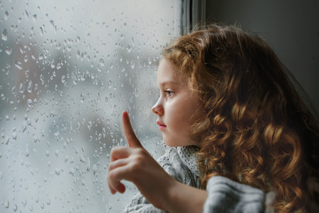 Photo for Sad little girl looking out the window on rain drops through wet glass autumn bad weather. - Royalty Free Image
