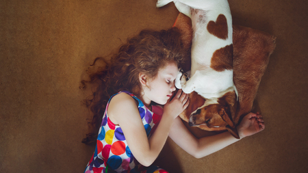 Foto de Cute girl hugging a puppy and sleeping on warm wooden floor. - Imagen libre de derechos