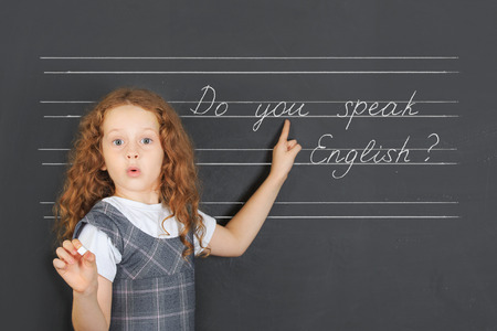 Photo for Surprised redhead girl asks a question -  Do you speak English, stand near blackboard in the classroom. Education concept. - Royalty Free Image