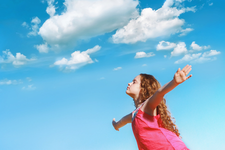 Foto de Little girl outstretched arms and closed her eyes  enjoying and breath fresh air. - Imagen libre de derechos