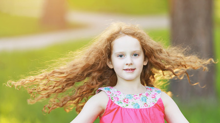 Photo for Happy little girl with a flying hairs is dancing in park. - Royalty Free Image