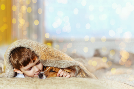 Photo pour Cute baby embracing and sleeping under wool blanket in early morning christmas day. - image libre de droit
