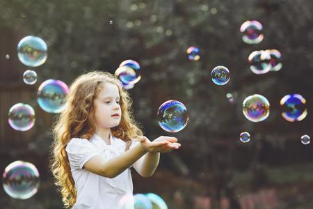 Photo pour Funny little girl catching soap bubbles - image libre de droit