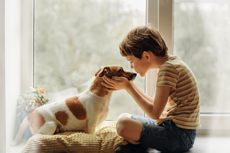 Foto de Little boy kisses the dog in nose on the window. Friendship, care, happiness, new year concept. - Imagen libre de derechos