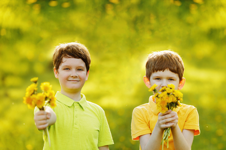 Photo for Little boys gives a bouquet yellow dandelions to his mother or girl friend. Mum, 8 march Day concept. - Royalty Free Image