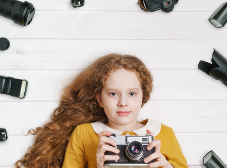 Photo for Little girl with retro photo cameras and photo accessoires lying on a wooden floor. - Royalty Free Image