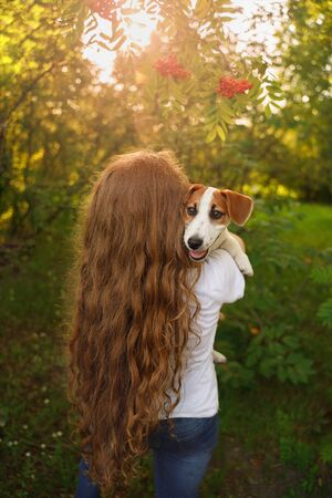 Foto de Cute girl with long curly hair embraces the puppy with a view from behind. - Imagen libre de derechos