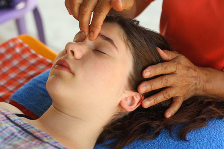 Photo pour head face thai massage teenager girl with closed eyes and massaging hands close up outdoor photo - image libre de droit