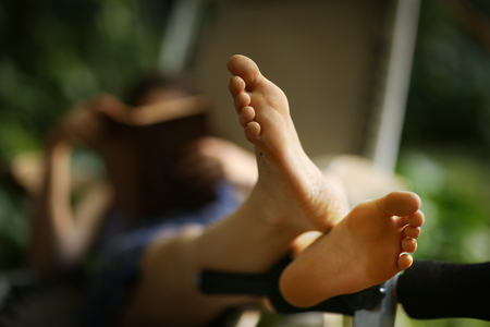 Foto de bare feet close up photo with book reading girl on deck chair on background - Imagen libre de derechos
