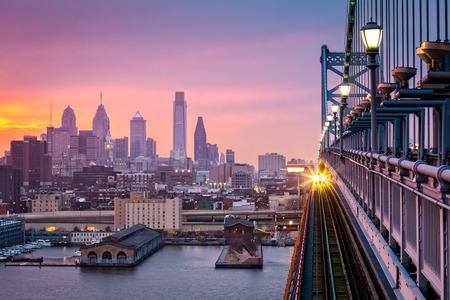 Foto per Philadelphia under a hazy purple sunset. An incoming train crosses Ben Franklin Bridge. - Immagine Royalty Free