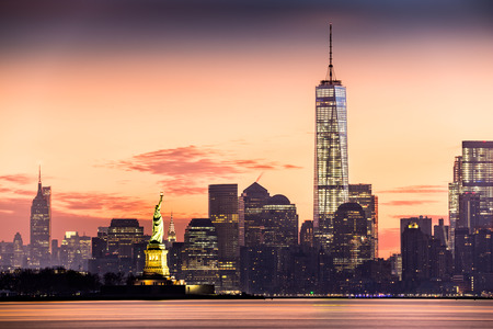 Foto de Lower Manhattan with Freedom Tower and The Statue of Liberty at sunrise - Imagen libre de derechos