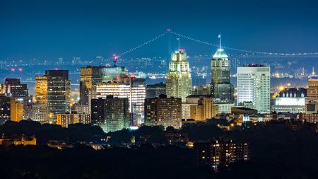 Photo for Newark, NJ, skyline on a hazy night with Verrazano Narrows bridge in the background. - Royalty Free Image