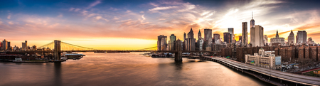 Photo for Brooklyn Bridge panorama at sunset. The iconic landmark spans between Brooklyn and the New York Financial District skyline, dominated by the Freedom Tower. - Royalty Free Image