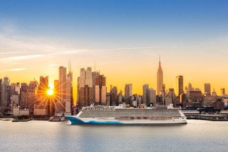 Foto de New York City skyline at sunrise, as viewed from Weehawken, along the 42nd street canyon. A large cruise ship sails Hudson river, while sun beams burst between the skyscrapers. - Imagen libre de derechos