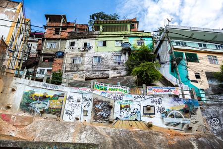 Foto de RIO DE JANEIRO - AUGUST 22 2015: Garbage collection place in Rochina Favela. Rocinha is the largest favela in Brazil. Graffiti decorates crammed hillside houses. - Imagen libre de derechos