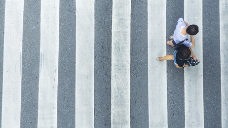 Photo for the top view of couple people walk across the pedestrian crosswalk in white and grey pattern  - Royalty Free Image