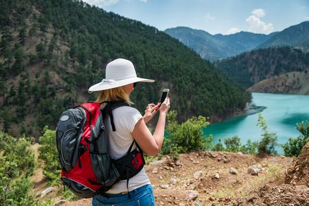 Foto für Woman backpacker using smart phone in mountains - Lizenzfreies Bild