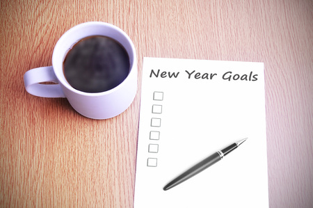 Photo pour Coffee on the table with note writing new year goals. - image libre de droit