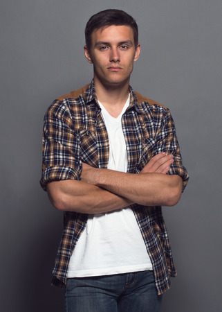 Photo for Portrait of a handsome young man - student urban casual stule, checkered shirt, arms crossed - Royalty Free Image