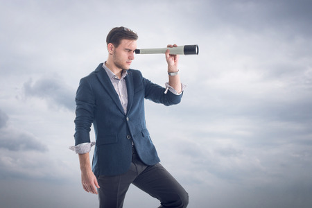 Photo pour Young attractive handsome businessman standing  with clouds around and looking through the spyglass to find new perspectives - image libre de droit