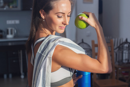Foto per Active athletic sportive woman with towel in sport outfit holding apple showing biceps healthy lifestyle. - Immagine Royalty Free