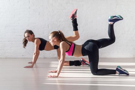 Foto de Healthy young sportswoman doing the exercises on all fours arching back straightening leg up concept sport, fitness, lifestyle. - Imagen libre de derechos