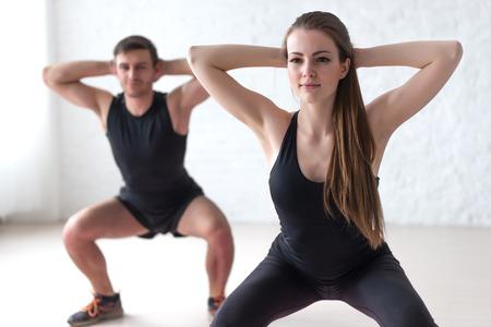 Foto de Fitness man and woman exercising squat exercise hands behind head concept sport, training, warming up and lifestyle. - Imagen libre de derechos